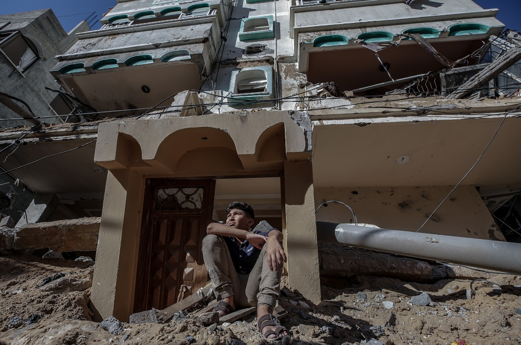 A Palestinian boy sits at the rubble of his family home destroyed after an Israeli strike in Gaza City, 13 May 2021.